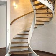 Деревянная спиральная лестница на тетивах, ступени и поручень - дуб, ограждение - ковка.