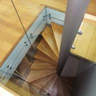 Квадратная в плане винтовая лестница со стеклянным ограждением.
