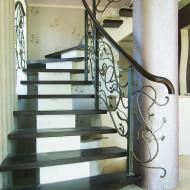 Лестница на центральном бетонном косоуре с кованым ограждением.