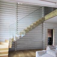 Современная лестница на металлическом каркасе со стеклянным ограждением.