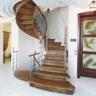 Деревянная лестница на гнутых косоурах с ограждением из нержавеющей стали.